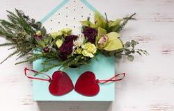 Twee rode harten op de blauwe envelop met bloemen stock foto