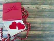 Twee rode harten op een houten achtergrond, rode doos, romantische parels Stock Afbeeldingen