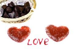 Twee rode harten op een witte mand als achtergrond met chocolade en t Stock Afbeelding