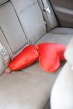 Twee rode hoofdkussens in de vorm van hart op de achterbank van auto Stock Afbeelding