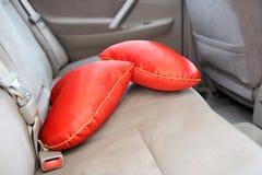 Twee rode hoofdkussens in de vorm van hart op de achterbank van auto Stock Afbeeldingen