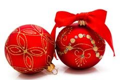 Twee rode Kerstmisballen met lint dat op een wit wordt geïsoleerd Stock Foto