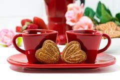 twee rode koffiekoppen en hart gevormde koekjes op witte achtergrond Royalty-vrije Stock Afbeelding