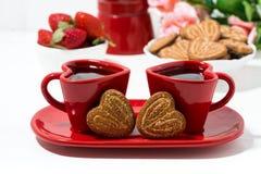 twee rode koffiekoppen en hart gevormde koekjes op witte lijst stock foto