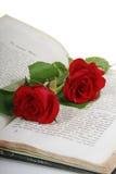 Twee rode rozen in een oud boek Stock Foto's