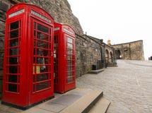 Twee rode telefooncellen op het Kasteel van Edinburgh Stock Foto