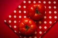 Twee rode tomaten die op de rode theedoek en de rode achtergrond liggen Royalty-vrije Stock Foto's