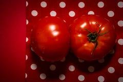 Twee rode tomaten die op de rode theedoek en de rode achtergrond liggen Royalty-vrije Stock Afbeeldingen