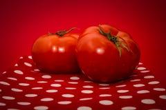 Twee rode tomaten die op de rode theedoek en de rode achtergrond liggen Royalty-vrije Stock Afbeelding