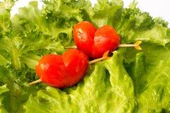 Twee rode tomatenkers op de groene ijsbergsalade en de citroen slidce stock afbeelding