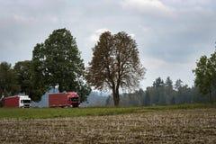 Twee rode vrachtwagens die langs een kleine weg lopen Stock Afbeeldingen