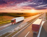 Twee rode vrachtwagens op weg bij zonsondergang Stock Foto