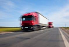 Twee rode vrachtwagens vage motie Royalty-vrije Stock Afbeelding