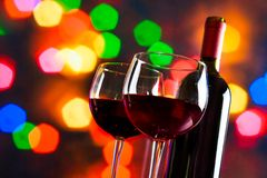 Twee rode wijnglazen dichtbij fles tegen kleurrijke bokeh steekt achtergrond aan Royalty-vrije Stock Afbeeldingen