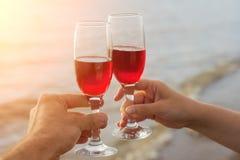 Twee rode wijnglazen in paar overhandigt silhouetten tegen overzeese zonsondergang stock foto's