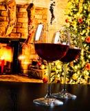 Twee rode wijnglazen tegen de achtergrond van de Kerstmisboom Royalty-vrije Stock Afbeeldingen