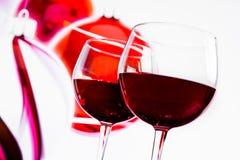 Twee rode wijnglazen tegen de achtergrond van de Kerstmisdecoratie Stock Foto