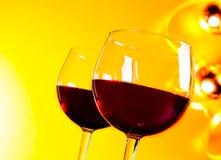 Twee rode wijnglazen tegen gouden lichtenachtergrond Stock Foto's