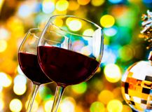 Twee rode wijnglazen tegen kleurrijke bokehlichten en de fonkelende achtergrond van de discobal Royalty-vrije Stock Afbeeldingen