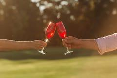 Twee rode wijnglazen in vrouwenhand en man hand op aardachtergrond royalty-vrije stock afbeelding