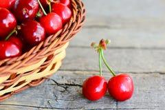 Twee rode zoete kersen, een mand met zoete kersen op een uitstekende houten lijst Het seizoenconcept van het de zomerfruit Stock Foto's