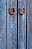 Twee roestige hotseshoe gelukkige symbolen op oude blauwe houten muur stock foto