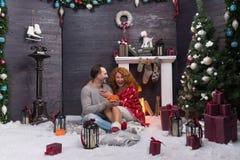 Twee romantische mensen die terwijl het vieren van Nieuwjaar dichtbij de open haard lachen royalty-vrije stock afbeeldingen