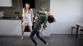 Twee rond actief voor de gek houdt de jonge voorvadersdans aan energieke muziek in de keuken, grappige vrouwen stock videobeelden