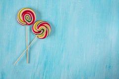 Twee ronde lollys met vele kleuren in een spiraal op turkooise achtergrond stock foto