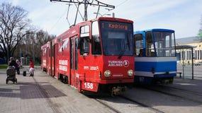 Twee rood-wit gekleurde trams die zich zij aan zij bij post in Tallinn, Estland bevinden Stock Afbeelding