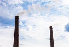 Twee rookstapels van het bedrijf tegen de bewolkte hemel Royalty-vrije Stock Fotografie