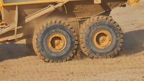 Twee roterende wielen van een vrachtwagen van de steengroevestortplaats met het vliegen stukken van vuil stock videobeelden