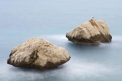 Twee rotsen en zeemeeuw in kalme overzees royalty-vrije stock afbeelding