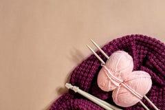 Twee roze breiend garenballen, breinaalden en en purpere gebreide plaid hoogste mening royalty-vrije stock foto's