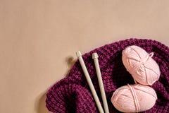 Twee roze breiend garenballen, breinaalden en en purpere gebreide plaid hoogste mening stock fotografie