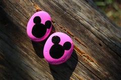 Twee roze geschilderde rotsen met zwarte Mickey Mouse-hoofden Stock Foto's