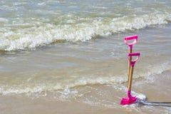Twee roze kinderachtige schoppen in het zand Stock Fotografie