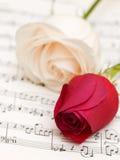 Twee rozen op de muzieknotenpagina Stock Afbeeldingen