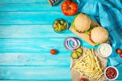 Twee rundvleesburgers, gebraden gerechtenaardappels en komkommer op blauwe houten lijst Stock Afbeeldingen