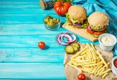 Twee rundvleesburgers, gebraden gerechtenaardappels en komkommer op blauwe houten lijst Royalty-vrije Stock Foto
