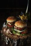Twee rundvleesburgers op een donkere achtergrond Royalty-vrije Stock Foto