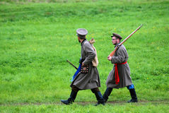 Twee Russische militair-reenactorsgang op groen gras Stock Fotografie
