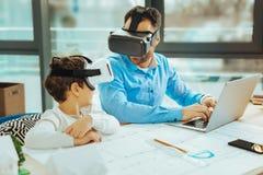Twee samen zitten die blijven en verwanten die in virtuele werkelijkheid worden verbonden royalty-vrije stock fotografie