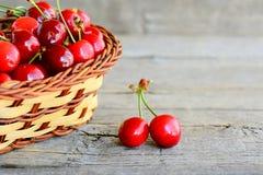 Twee sappige zoete kersen, rieten mand met zoete kersen op een oude houten lijst Voedsel van het de zomer het natuurlijke fruit Royalty-vrije Stock Foto's