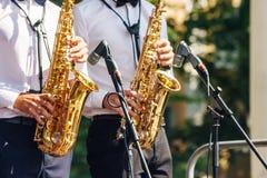 Twee saxofonisten die bij een jazzfestival spelen in een stad parkeren royalty-vrije stock foto