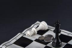 Twee schaakkoningen die zich voor elkaar, muntstukken tussen t bevinden royalty-vrije stock afbeelding