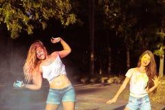 Twee schitterende jonge vrouwenvrienden die pret met het exploderen Holi hebben Royalty-vrije Stock Afbeeldingen