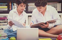 Twee schooljongens in de bibliotheek Stock Foto's