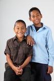 Twee schooljongens stellen gelukkig samen in studio Royalty-vrije Stock Afbeeldingen
