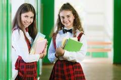 Twee schoolmeisjes bevinden zich in de gang met boeken royalty-vrije stock foto